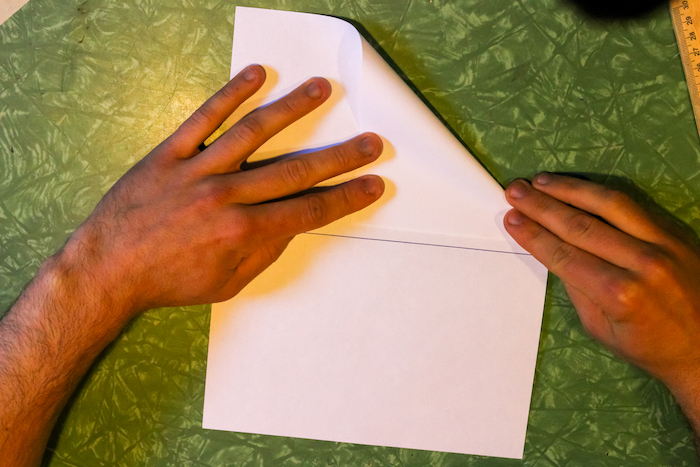 Folding the right corner almost to the middle of the page with hands.