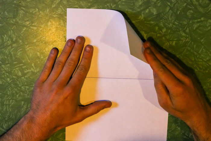 Folding right corner of paper with hand.