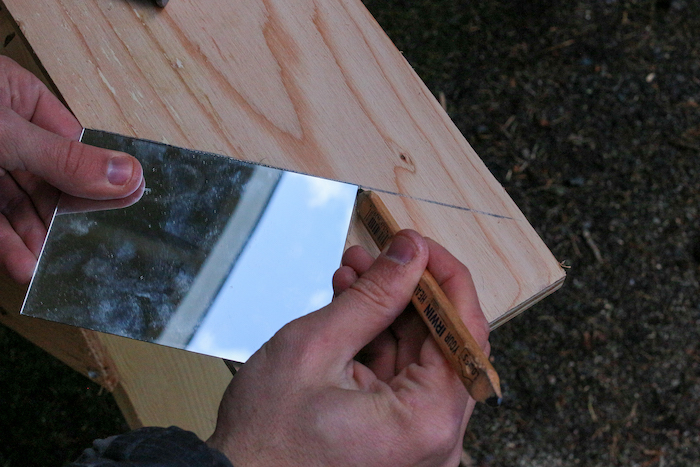 Marking the mirror with pencil placed on plywood.