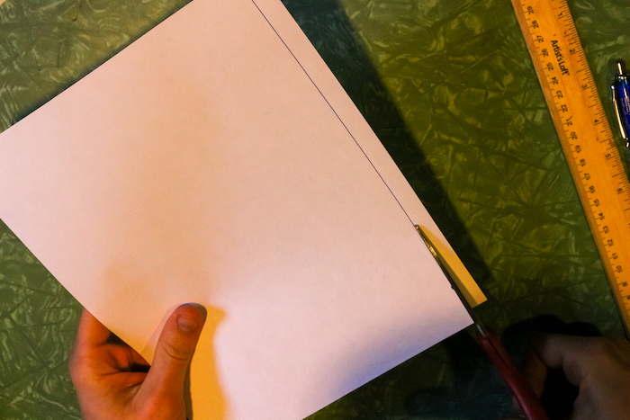 Cutting paper with knife along with pen and scale.