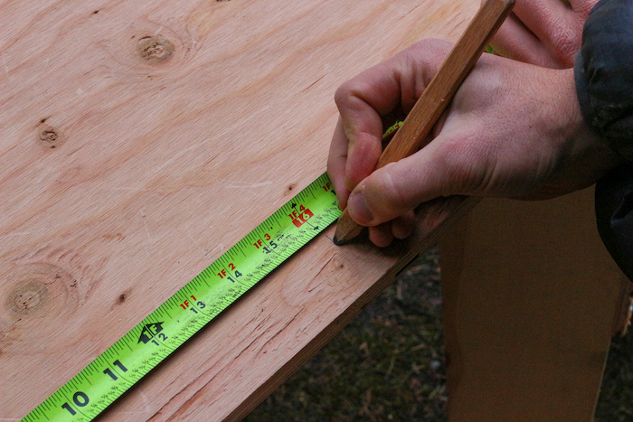 Measuring the plywood with the help of pencil and scale.