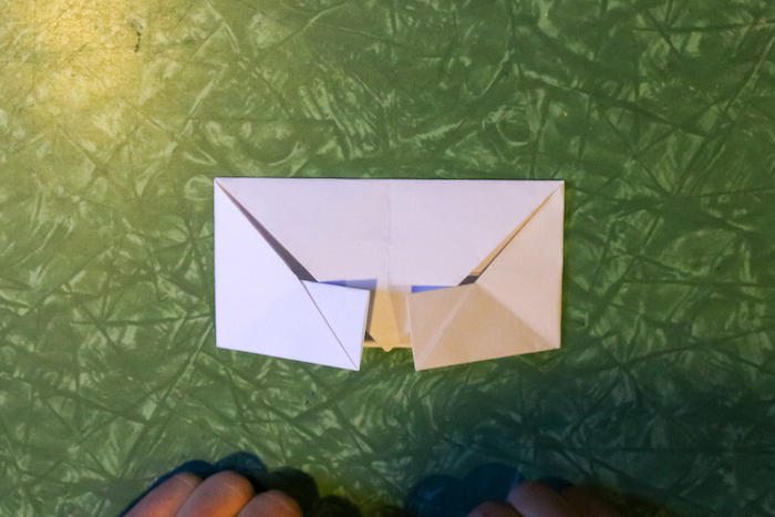 Folding the sides in to create a square edge to the envelope.