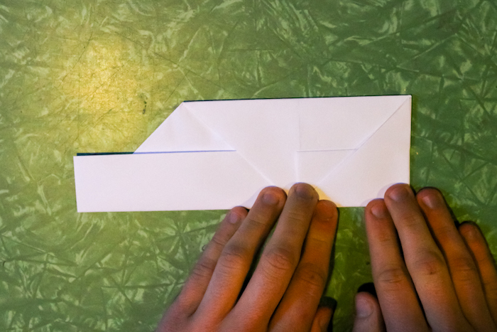 Folding the sides in to create a square edge to the paper.