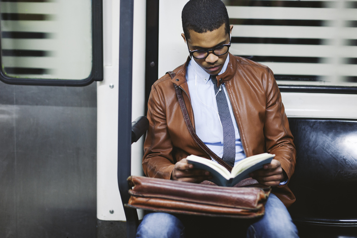 A boy reading a book while traveling in subways.