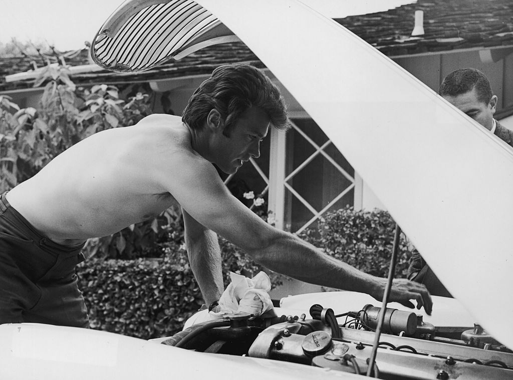 A man repairing the engine of the vehicle.