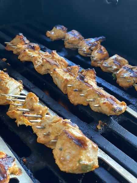 Chicken pieces on skewer are getting grilled.
