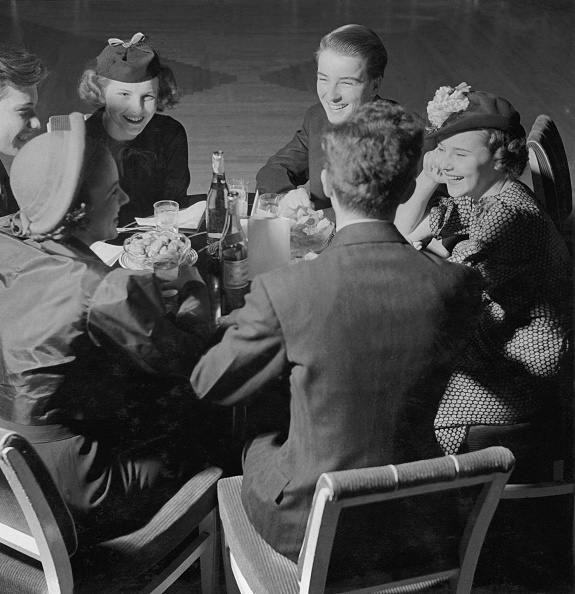 A bunch of girls and Gentlemen are sitting on a table enjoying their dinner.