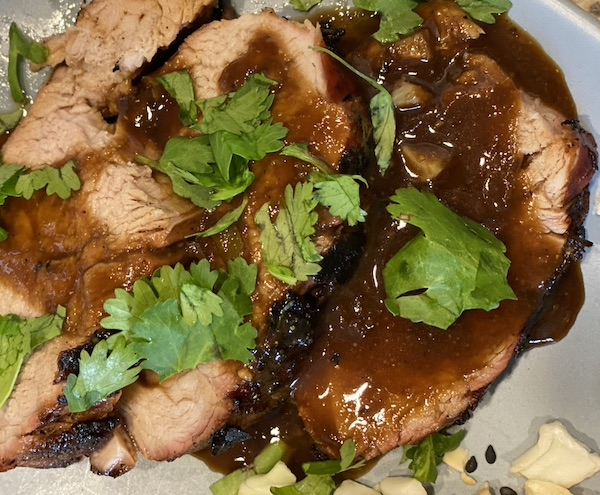 Peanut butter pork loinserved with sauce with cilantro topping.