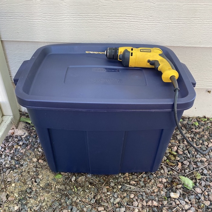 A large Plastic bin with a drill machine is placed on rocks.