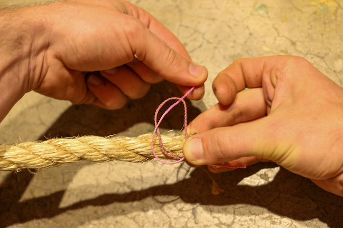 Take the end of your twine furthest from the end of your rope and pass it through the loop.