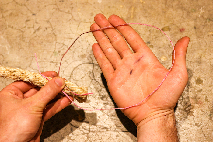A man holding two ropes under thumb and loop in another hand.