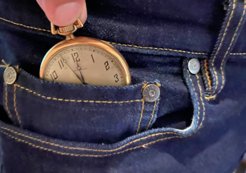 A guy putting stop watch in the little pocket of jeans.