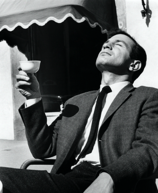 Man holding a cup and enjoying sunlight.