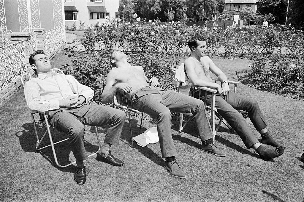 Three persons sitting on a chair and taking sunbath.