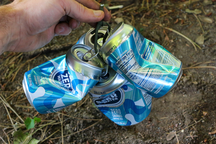 A man holding some empty cans with a sting.
