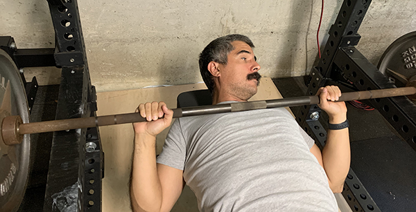 Man resetting barbell on safety arms.