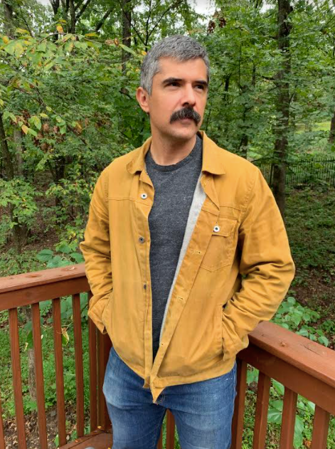 man wearing flint and tinder trucker jacket with wooded background.