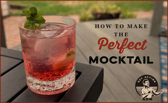 mocktail with red color and mint sprig on a patio table.