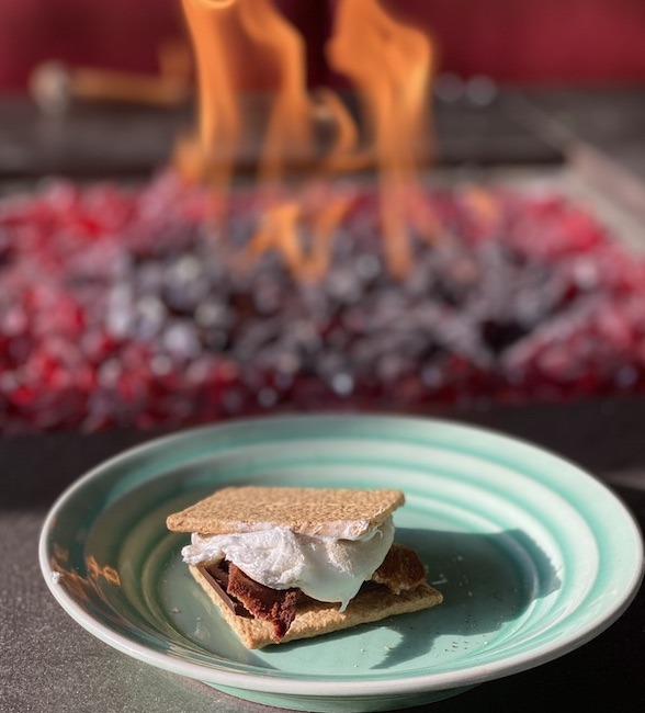 smore with bacon on it and fire in the background.