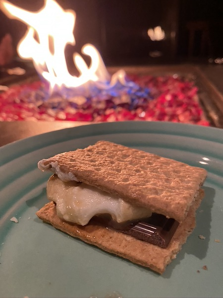 smore with marshmallow dipped in baileys and fire in the background.