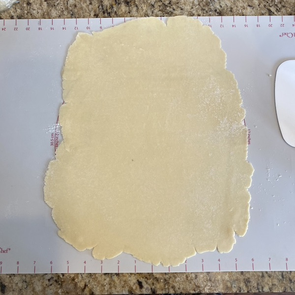 rolled out pie dough on a baking mat.