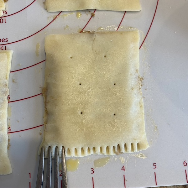 crimping edges of homemade pop tarts with fork.