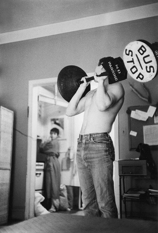 Steve McQueen shoulder pressing a bus stop sign